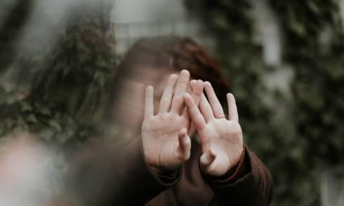 Ein Kind, das sein Gesicht mit der Hand abdeckt